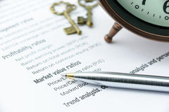 Blauer Kugelschreiber auf Check-Listen einer Finanzkoeffizientenanalyse mit einer antiken Uhr und zwei Weinlesemessingschlüsseln Lizenzfreie Stockfotos