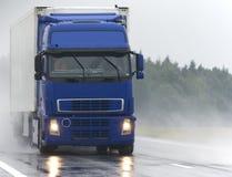 Blauer Lastwagen auf nasser Straße lizenzfreie stockbilder