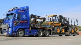 Blauer LKW Volvos FH13, der Ponsse-Forstwirtschafts-Maschinerie schleppt Stockbild