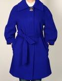 Blauer Mantel mit Gurt auf grauem Hintergrund Oberbekleidung, Sammlung von Frühling 2017 Lizenzfreie Stockfotos