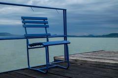 Blauer Metallstuhl auf hölzernem Pier am Balaton See Lizenzfreie Stockbilder