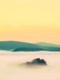 Blauer nebelhafter Morgen, Ansicht über Felsen zum tiefen Tal voll der träumerischen Frühlingslandschaft des hellen Nebels innerh Lizenzfreies Stockbild