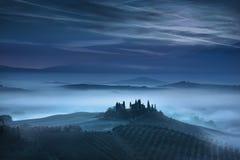 Blauer nebeliger Morgen Toskana, Ackerland und Zypressenbäume Italien Stockfotografie