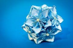 Blauer Origami blüht Ball auf dem blauen Hintergrund Stockfoto