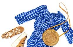 Blauer Overall der stilvollen modischen weiblichen Sommerkleidungs Kleider, Rattantaschen-Zweigeukalyptus der Sandalen runder auf lizenzfreie stockfotografie