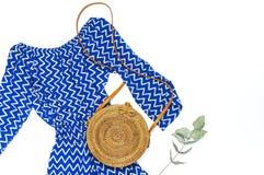 Blauer Overall der stilvollen modischen weiblichen Sommerkleidungs Kleider, runder Rattantaschen-Zweigeukalyptus auf modischem Hi stockfotos