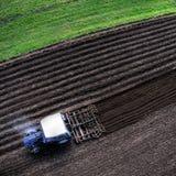 Blauer pflügender Traktor, von der Luftdraufsicht Stockfotos