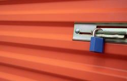 Blauer Plastikverschluß auf einer orange Selbstspeichereinheitstür stockfoto