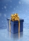Blauer Präsentkarton auf Eis in den Schneefällen Stockfotos