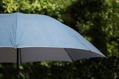 blauer Regenschirm im Regen Stockbilder