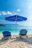 Blauer Regenschirm und Solarien auf dem beatch Lizenzfreie Stockfotos
