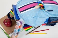 Blauer Rucksack voll Zubehör auf Weiß Stockfotografie