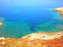 Blauer ruhiger See mit einem Strand verloren Lizenzfreie Stockfotografie