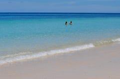 Blauer ruhiger See mit weißem Sand Stockbild