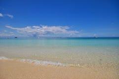 Blauer ruhiger See mit weißem Sand Stockfotos