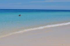 Blauer ruhiger See mit weißem Sand Stockbilder