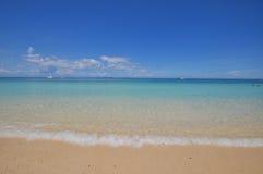 Blauer ruhiger See mit weißem Sand Lizenzfreie Stockfotos