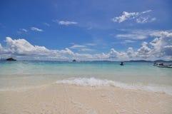 Blauer ruhiger See mit weißem Sand Stockfotografie
