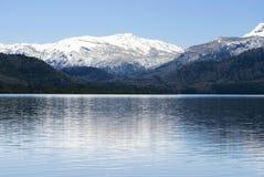 Blauer ruhiger See und Schnee deckten Berg ab stockfotos