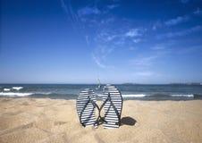 Blauer SandaleFlipflop auf dem Sandstrand mit blauem See- und Himmelhintergrund in Sommerferien Kopieren Sie Platz Stockfoto