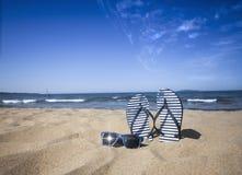 Blauer SandaleFlipflop und Sonnenbrille auf dem Sand setzt mit blauem See- und Himmelhintergrund in Sommerferien auf den Strand K Stockfotografie