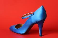 Blauer Schuh auf rotem Hintergrund Lizenzfreie Stockfotos