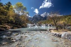 Blauer See in den Himalajatibet-Bergen mit Bäumen und im blauen Himmel in China am Herbst lizenzfreies stockfoto