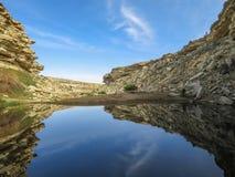 Blauer See in der Wüste unter den Felsen Apfelbaum, Sonne, Blumen, Wolken, Wiese? lizenzfreies stockfoto