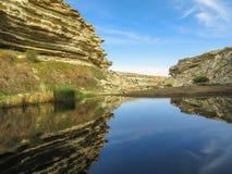 Blauer See in der Wüste unter den Felsen Apfelbaum, Sonne, Blumen, Wolken, Wiese? stockfotografie