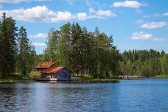 Blauer See mit ländlichem Haus Stockbild