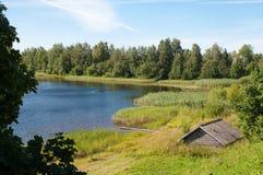 Blauer See mit ländlichem Haus Stockfotografie