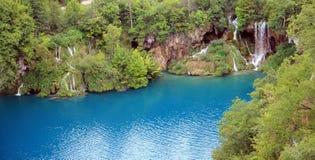 Blauer See mit Wald und Wasserfall Stockfotos