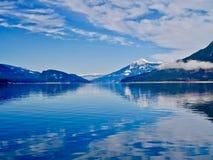 Blauer See und blaue schneebedeckte Berge Stockfoto