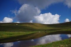 Blauer See und blauer Himmel mit Wolken, in den Alpen stockfotografie