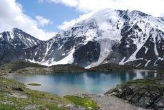 Blauer See vor geschneiten Hügeln Stockfotografie