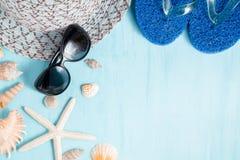 Blauer Seehintergrund mit Hut, Sonnenbrille und Muscheln, Sommerferien und Ferienzeitkonzept lizenzfreie stockbilder