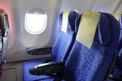 Blauer Sitz und Fenster des Flugzeuges Stockbild