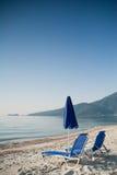 Blauer Sommerregenschirm mit zwei Stühlen auf blauem Himmel Stockfoto
