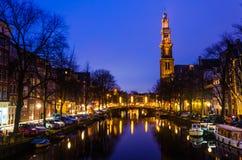 Blauer Sonnenaufgang des Morgens auf Amsterdam-Kanal mit Kirchenglocketurm auf dem Hintergrundhorizont stockfoto