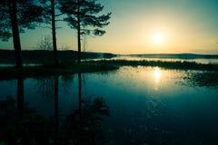 Blauer Sonnenuntergang über dem See, der überlief Stockfotografie