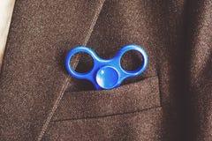 Blauer Spinner in der Tasche des Blazergeschäftsgeschäftsmannes stockbilder