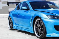 Blauer Sportwagen auf Rennweise Nahaufnahmegefangennahme lizenzfreie stockfotos