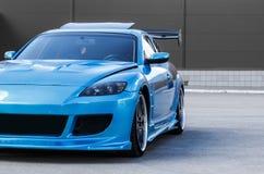 Blauer Sportwagen auf Rennweise Nahaufnahmegefangennahme stockfotos