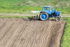 Blauer staubiger Traktor mit dem Saatbeetlandwirt, der am Rand des frisch gepflogenen und bebauten Feldes steht, Boden bereitete  Lizenzfreie Stockbilder