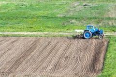 Blauer staubiger Traktor mit dem Saatbeetlandwirt, der am Rand steht Lizenzfreie Stockfotos