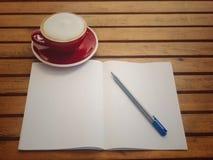 Blauer Stift auf Weißbuch mit heißem Kaffee in der roten Schale auf Holztisch haben Raum für Beschaffenheit Stockbild