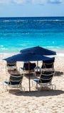 Blauer Strandschirm auf dem Ozean mit Strandstühlen Stockbild