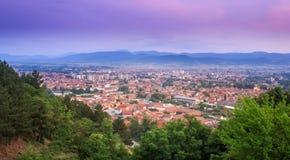 Blauer Stundenhimmel über Pirot-Stadt und grünen Vordergrundbäumen lizenzfreies stockfoto