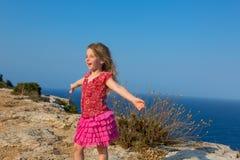 Blauer Tag mit den geöffneten Händen des Kindmädchens zum Wind Stockfotografie
