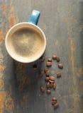 Blauer Tasse Kaffee auf Kandidatenliste mit Bohnen lizenzfreie stockfotos